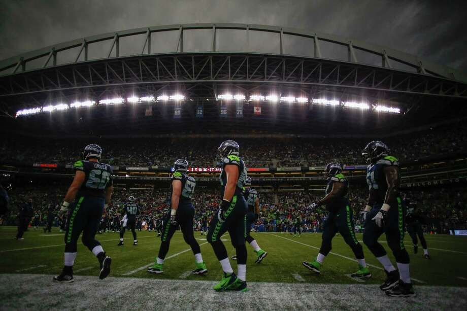 SEATTLE, WA - SEPTEMBER 15:  Members of the Seattle Seahawks return to the field after a rain delay during the game against the San Francisco 49ers at CenturyLink Field on September 15, 2013 in Seattle, Washington. Photo: Otto Greule Jr, Getty Images / 2013 Getty Images
