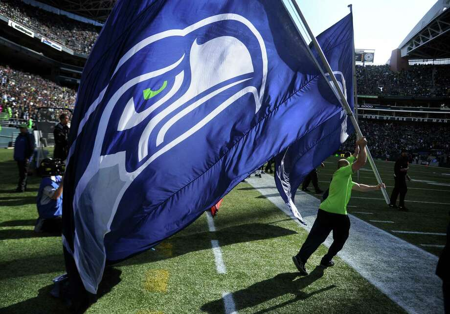 SEATTLE, WA. - SEPTEMBER 22: A cheerleader runs out onto the field with a Seattle Seahawks flag during the third quarter of the game between the Seattle Seahawks and the Jacksonville Jaguars at CenturyLink Field on September 22, 2013 in Seattle, Washington. Photo: Steve Dykes, Getty Images / 2013 Steve Dykes