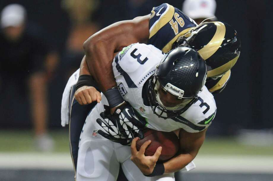 ST. LOUIS, MO - OCTOBER 28: Russell Wilson #3 of the Seattle Seahawks is sacked during the first quarter by Robert Quinn #94 of the St. Louis Rams at the Edward Jones Dome on October 28, 2013 in St. Louis, Missouri. Photo: Michael Thomas, Getty Images / 2013 Getty Images