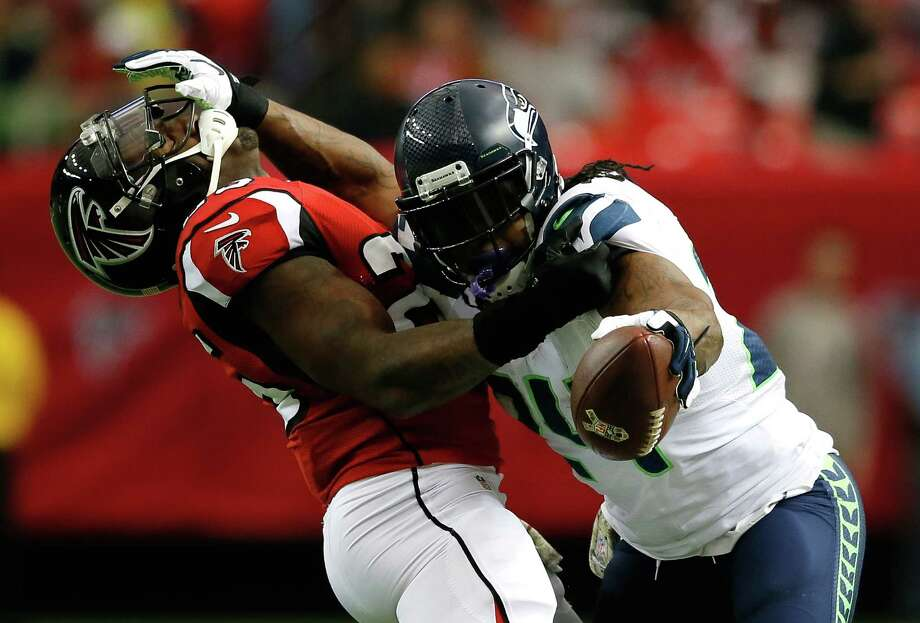 ATLANTA, GA - NOVEMBER 10:  Marshawn Lynch #24 of the Seattle Seahawks stiff arms William Moore #25 of the Atlanta Falcons at Georgia Dome on November 10, 2013 in Atlanta, Georgia. Photo: Kevin C. Cox, Getty Images / 2013 Getty Images