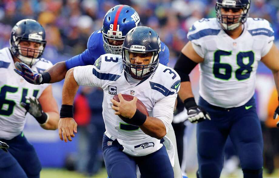 EAST RUTHERFORD, NJ - DECEMBER 15:  (NEW YORK DAILIES OUT)    Russell Wilson #3 of the Seattle Seahawks in action against the New York Giants on December 15, 2013 at MetLife Stadium in East Rutherford, New Jersey. The Seahawks defeated the Giants 23-0.  (Photo by Jim McIsaac/Getty Images) *** Local Caption *** Russell Wilson Photo: Jim McIsaac, Getty Images / 2013 Jim McIsaac