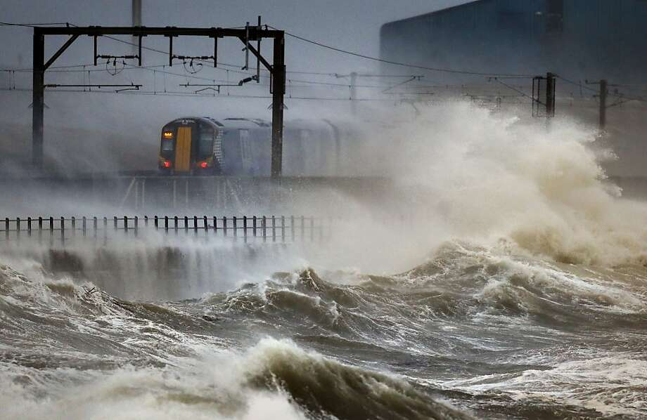 A train passes along the storm-socked coast in Saltcoats, Scotland, as Britain braces for a combination of high 