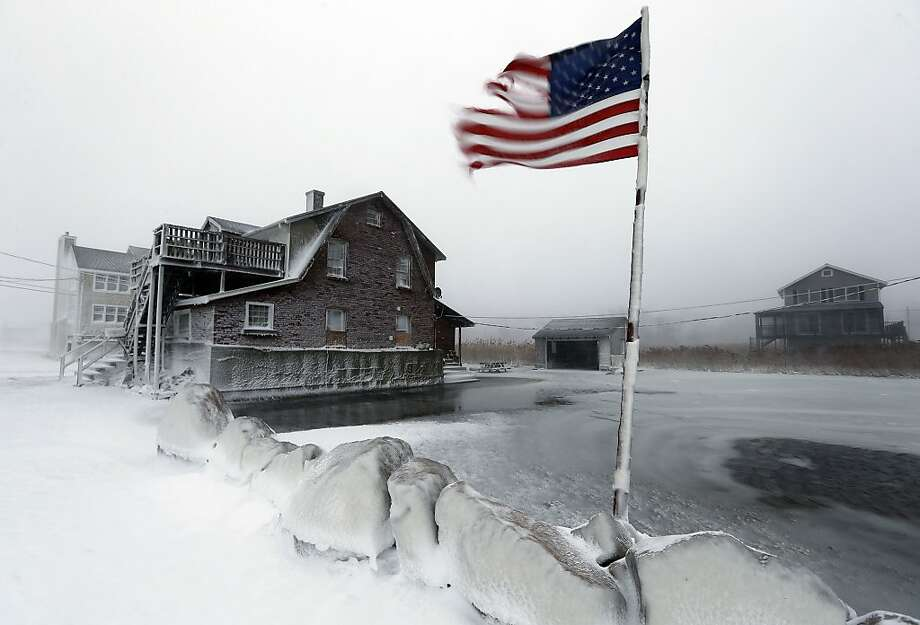 Cold Glory: A tattered flag flies in a flooded yard along the windswept shore in Scituate, Mass. A blustery 