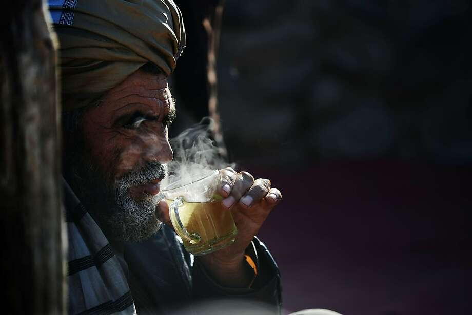 Steaming brew: An Afghan man sips tea on a cold winter morning at a livestock market outside Kabul. Hundreds of 