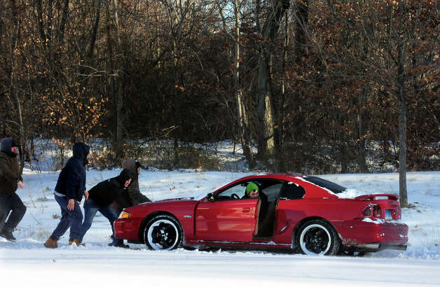 A motorist gets a little push after getting stuck near the Lowe's off of Old Gate Lane in Milford, Conn. on Friday January 3, 2014. Photo: Christian Abraham / Connecticut Post