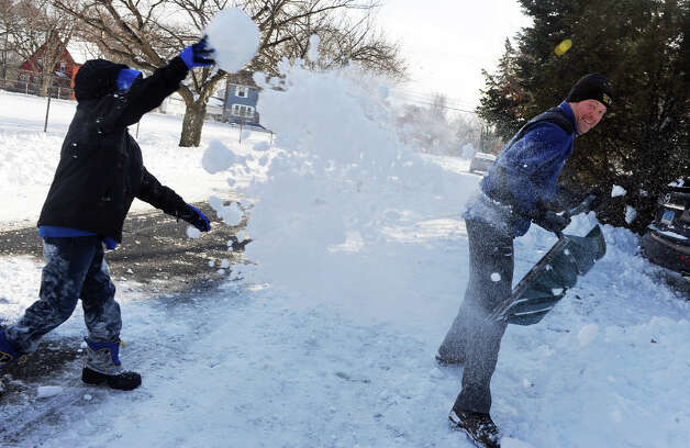 Nolan McCormack, 10, left, throws snow at Mike Harwood as they have a snow fight with Nolan's brothers and friends on Colony Street in Fairfield, Conn. on Friday January 3, 2014. Photo: Christian Abraham / Connecticut Post