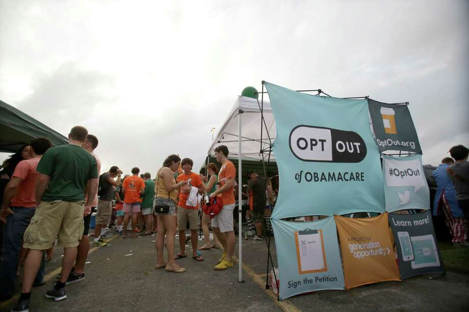 Tailgaters at a college football game in the fall hung out near a row of tents set up by Generation Opportunity, a national conservative organization that targets young adults, with the goal of getting students to opt out of Obama's new health law. Photo: Wilfredo Lee, STF / AP