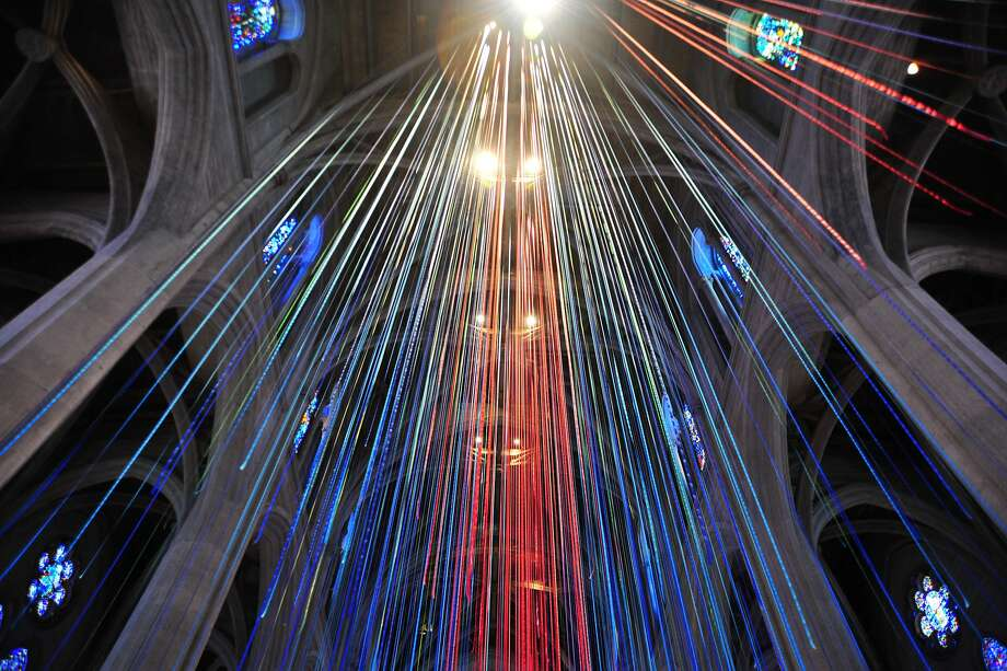"The ""Graced With Light"" installation consists of about 1,100 strands of ribbon, each 86 feet in length, in shades of blue, green and red. They cascade from the cathedral's attic. Photo: Fiestaban Photography"