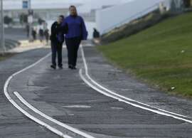 Pedestrians stroll along a defunct railroad line at Aquatic Park in San Francisco, Calif. on Thursday, Jan. 2, 2014.