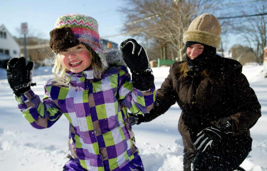 Marisa Olander, 5, plays in the snow at Daskam Park in Stamford, Conn., with her mother, Susan, on Friday, January 3, 2014. Photo: Lindsay Perry / Stamford Advocate