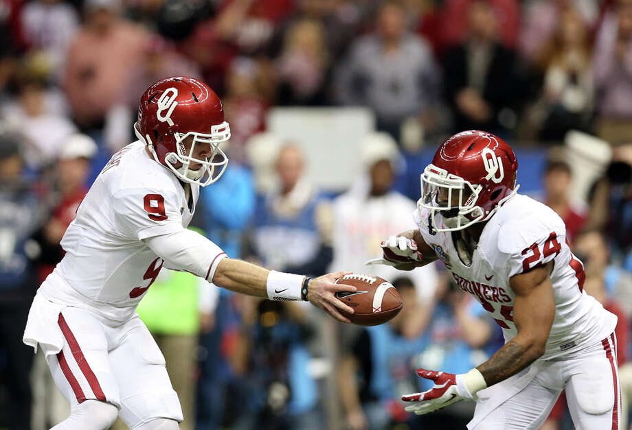Trevor Knight #9 of the Oklahoma Sooners hands the ball off to Brennan Clay #24 against the Alabama Crimson Tide during the Allstate Sugar Bowl at the Mercedes-Benz Superdome on January 2, 2014 in New Orleans. Photo: Sean Gardner, Getty Images / 2014 Getty Images