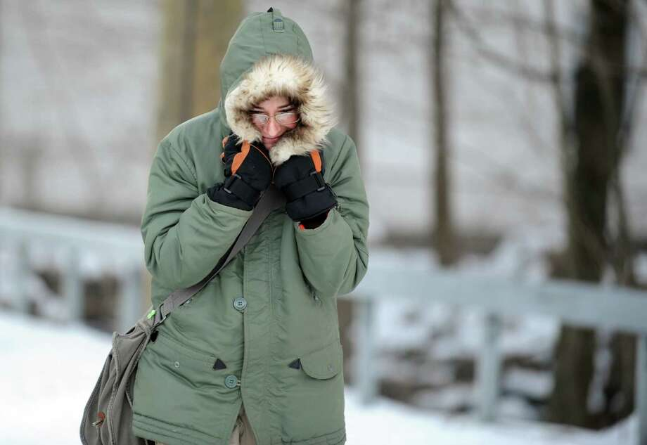 Mary Fritz, of Shelton, pulls her hood tight around her face as she walks  home from the post office Friday, Jan. 3, 2014 in Shelton, Conn.  Fritz said she dug her car out of the snow only to find the battery had died from the severe cold temps. Photo: Autumn Driscoll / Connecticut Post