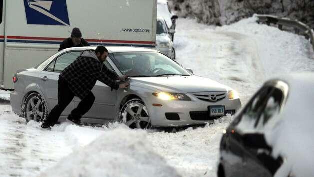 Good samaritans help a driver stuck in the snow Friday, Jan. 3, 2014 in Shelton, Conn. Photo: Autumn Driscoll / Connecticut Post