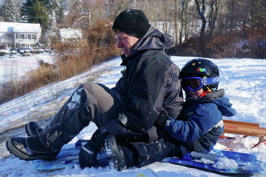 David Crosby and 4-year-old son Jack prepare for a downhill ride at Western Greenwich Civic Center Park. Photo: Paul Schott, Greenwich Time / Greenwich Time