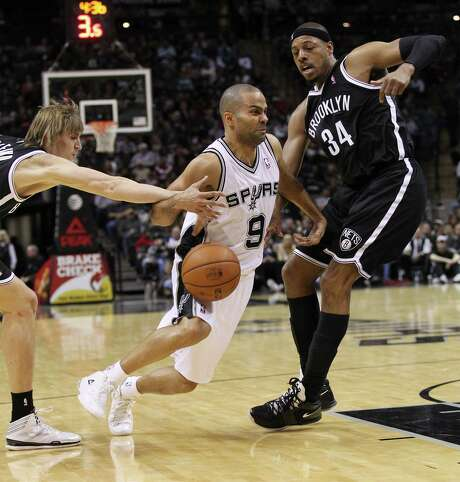 Spurs' Tony Parker (09) gets fouled while driving to the basket by Brooklyn Nets' Andrei Kirilenko (47) in the second half at the AT&T Center on Tuesday, Dec. 31, 2013. Spurs win 113-92. Photo: Kin Man Hui, San Antonio Express-News / ©2013 San Antonio Express-News