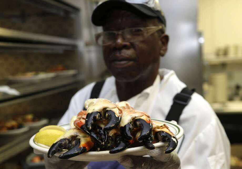 Florida: Eugene Green holds up a plate of stone crabs while working in the kitchen at Joe's Stone Crab restaurant in Miami Beach, Fla. Green has worked for the restaurant for over forty years. Joe's Stone Crab has been family-owned from the start when it opened in 1913 as a mom-and-pop fish house. Today, it''s a must-stop spot where wearing a bib over fine-dining attire is the norm. Photo: Lynne Sladky, Associated Press