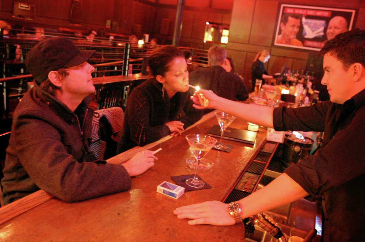 Smoking in bars was once a welcomed, assumed activity in Seattle. Pictured are smokers at Tini Bigs in Queen Anne on Oct. 31, 2005, a month before voters passed Washington's ban on smoking in public places. It took effect in December of 2005 and also banned smoking outside within 25 feet of doors, windows and vents.