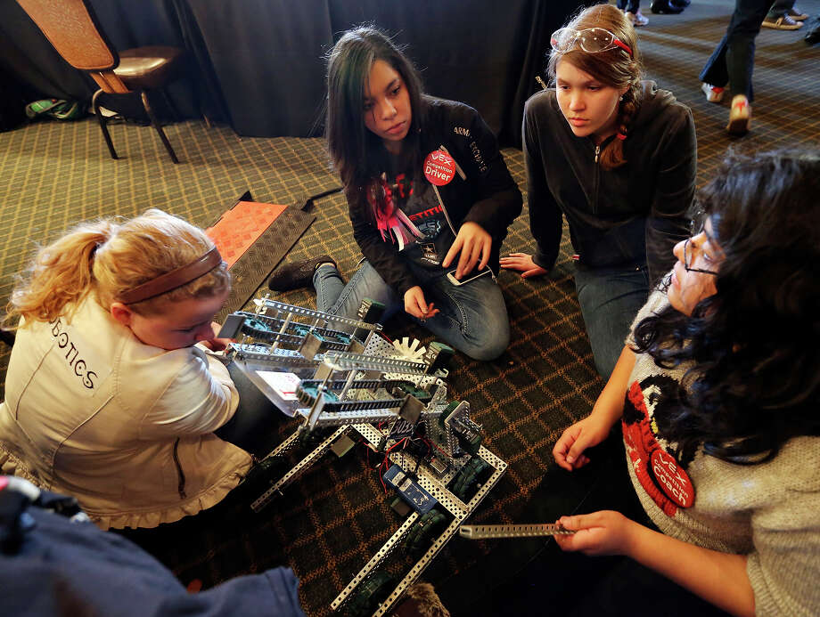 The Women Are Robotic team from Roosevelt high school  Chantal Borchardt, 15, (from left), Odmara Hernandez, 17, Ashley Offret, 16, and Itzel Romero, 16,  work on their robot between matches during the VEX Robotics Competition sponsored by the U.S. Army All-American Bowl Friday Jan. 3, 2013 at Sunset Station. Middle and high school students from all over Texas took part in the event. Photo: Edward A. Ornelas, San Antonio Express-News / © 2013 San Antonio Express-News