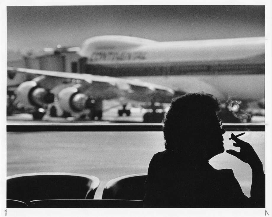 This woman is smoking inside Sea-Tac Airport on Feb. 25, 1990, the first day a federal smoking ban on most flights took effect. Sea-Tac shut down most of its separate smoking sections in 1993 and has since become entirely smoke-free. Except for two remote locations outside.  Photo: Copyright MOHAI, Seattle Post-Intelliencer Collection,