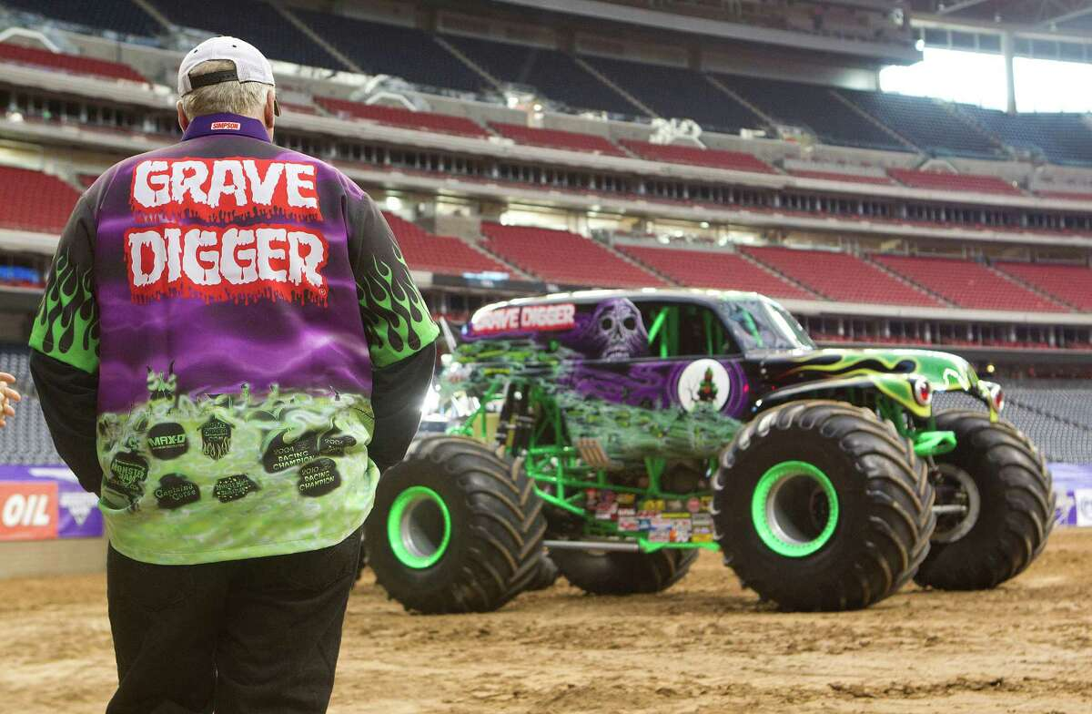Grave Digger driver Dennis Anderson stands near his truck before meeting with the media in Reliant Stadium Friday, Jan. 3, 2014, in Houston. The Monster Jam event Saturday features 24 monster trucks including Grave Digger, Scooby-Doo, Toro Loco, and Mohawk Warrior. The trucks will compete in a race and freestyle event.