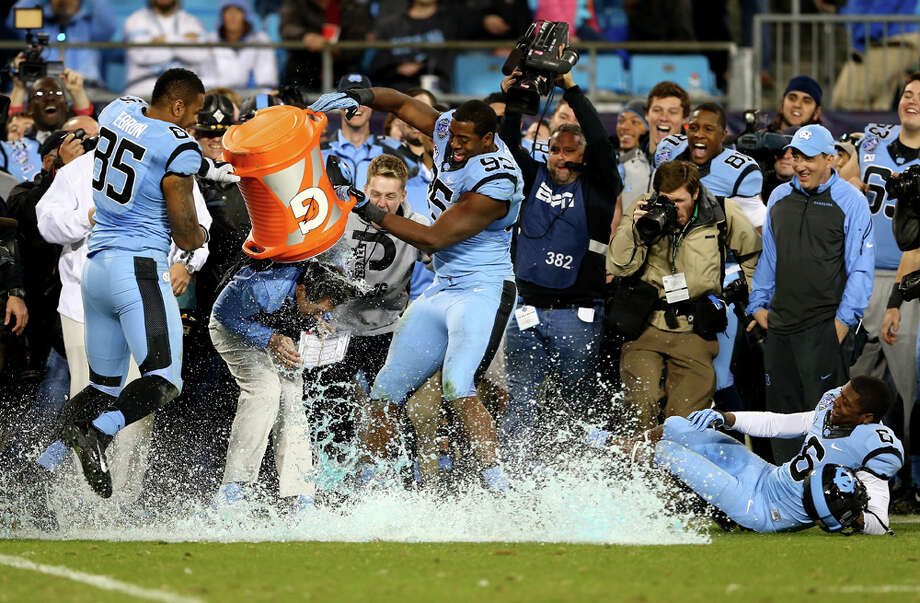 North Carolina's Kareem Martin (95) and Eric Ebron (85) celebrate as they dunk head coach Larry Fedora with Gatorade after defeating Cincinnati 39-17 in the Belk Bowl at Bank of America Stadium on Dec. 28, 2013, in Charlotte, N.C. Photo: Streeter Lecka, Getty Images / 2013 Getty Images