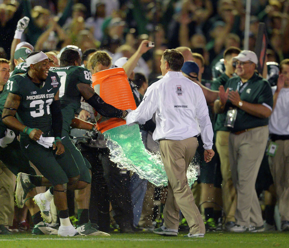 Michigan State head coach Mark Dantonio is missed by getting hit by a bucket of energy drink after defeating Stanford 24-20 at the Rose Bowl Game presented by VIZIO on Jan. 1, 2014, in Pasadena, Calif.