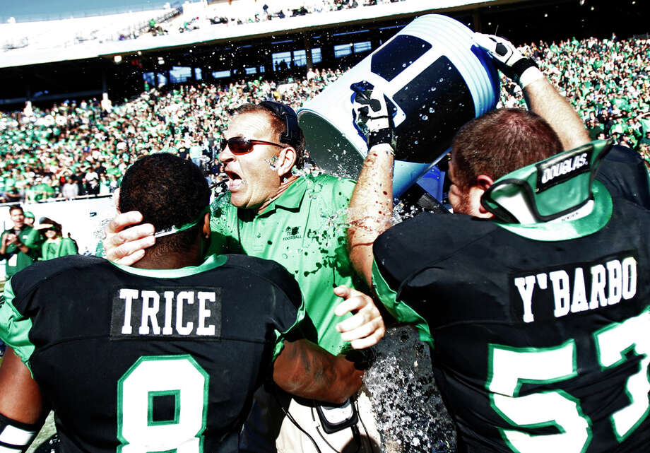 North Texas defensive back Marcus Trice (8) and offensive lineman Mason Y'Barbo (57) douse head coach Dan McCarney following their 36-14 win over UNLV in the Heart of Dallas Bowl, Jan. 1, 2014, in Dallas. Photo: Mike Stone, Associated Press / FR159596 AP