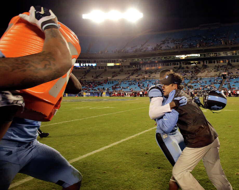 North Carolina's Sean Tapley (left) tries to hold head coach Larry Fedora as the team tries to dunk the coach in the closing seconds of the Belk Bowl on Dec. 28, 2013, in Charlotte, N.C. North Carolina defeated Cincinnati 39-17. Photo: Nell Redmond, Associated Press / FR25171 AP