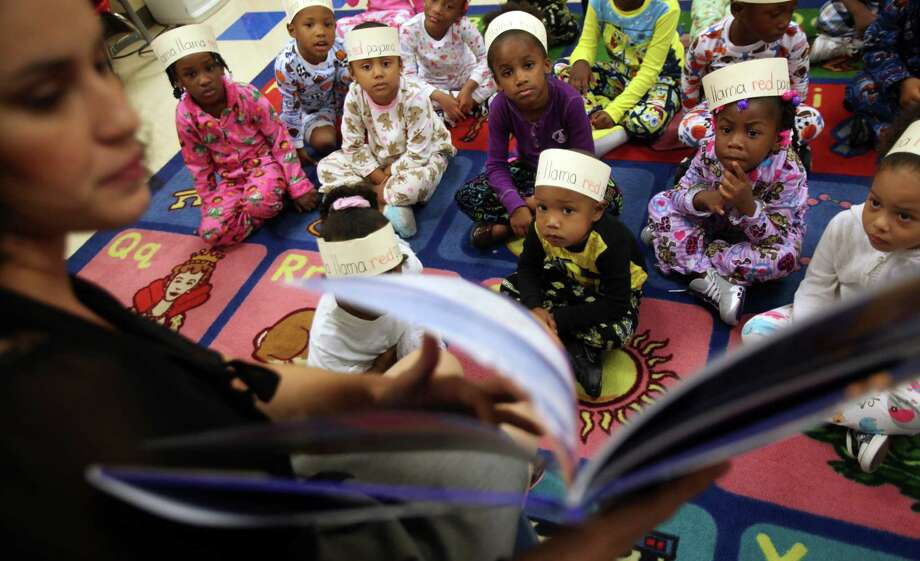 "Pre-kindergarden students listen to Melissa Martinez read their favorite book ""Llama Llama Red Pajama"" in their pajama's as they participate in setting a world reading record at Thompson Elementary School on Thursday, Oct. 6, 2011, in Houston. The students at HISD and across the country will ""read for the record"" as part of a major effort promoted by the Pearson Foundation to raise awareness for the need to read to children at the youngest ages. For the first time ever, children nationwide will also attempt to break the record for the largest number of children being read to from a digital story online.   ( Mayra Beltran / Houston Chronicle ) Photo: Mayra Beltran, Staff / © 2011 Houston Chronicle"