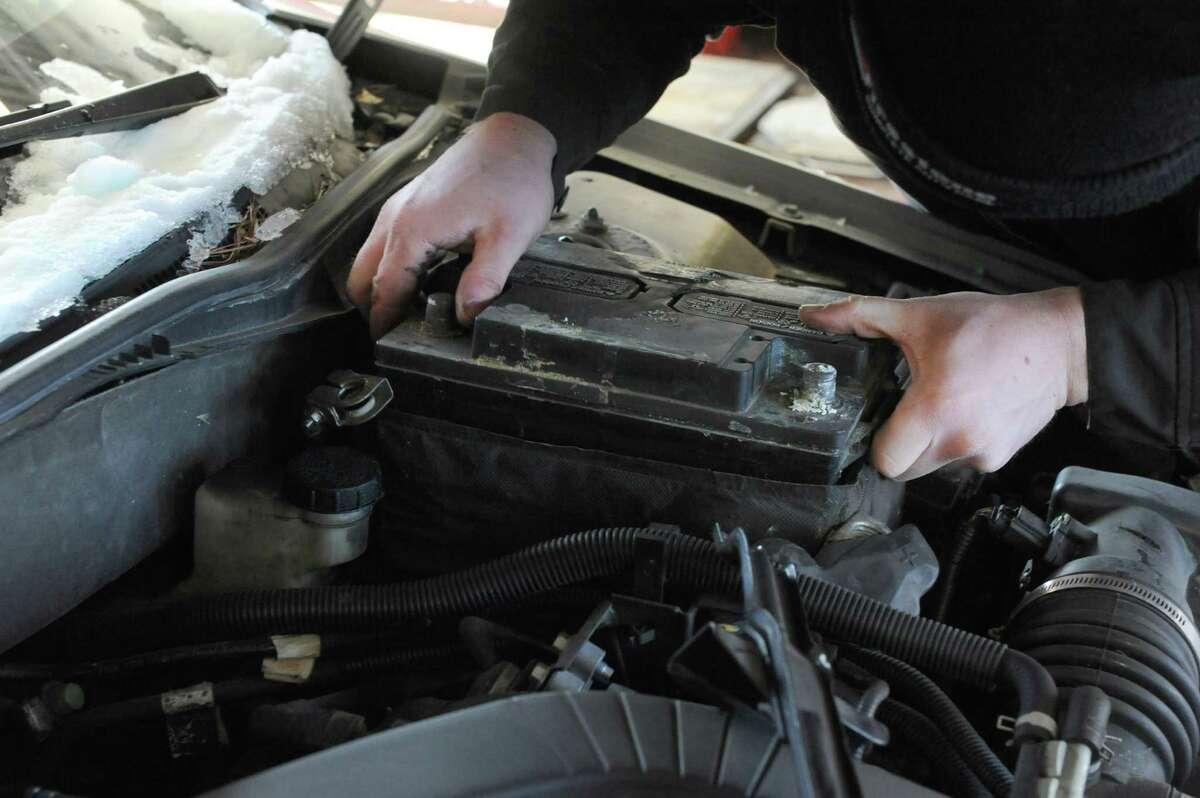 Mechanic Dave Bogdan installs a car battery at Firestone on Friday Jan. 3, 2014 in Colonie , N.Y. (Michael P. Farrell/Times Union)