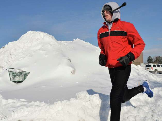 Franklin Pierce track team member Jon Holmes, 18, of Colonie, runs past piled up snow at Colonie Center as he keeps up his practice routine during winter break Friday Jan. 3, 2014, in Colonie, NY.  (John Carl D'Annibale / Times Union) Photo: John Carl D'Annibale / 00025215A