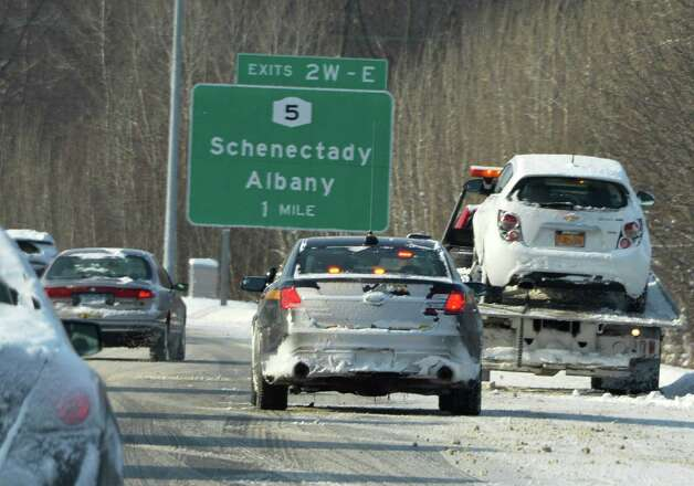 A police car stands by as a wrecker removes a car from the southbound lanes of the Northway Friday Jan. 3, 2014, in Colonie, NY.  (John Carl D'Annibale / Times Union) Photo: John Carl D'Annibale / 00025215A