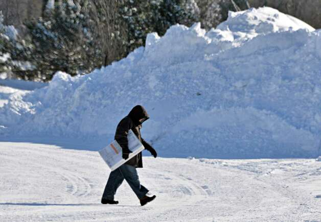 A man carries a box across past mounds of plowed snow in the parking lot at Colonie Center Friday Jan. 3, 2014, in Colonie, NY.  (John Carl D'Annibale / Times Union) Photo: John Carl D'Annibale / 00025215A