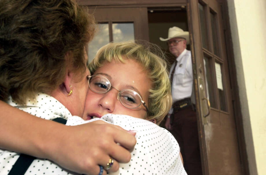 A Val Verde County law enforcement official opens the courthouse as Krystal Surles, 10, hugs her grandmother, Myrna Wright, on her way into the Val Verde County Justice Center on Sept. 12, 2000. Surles, who survived an attack by Sells, will testify against him in Sells' capital murder trial. Photo: GLORIA FERNIZ, San Antonio Express-News / SAN ANTONIO EXPRESS-NEWS