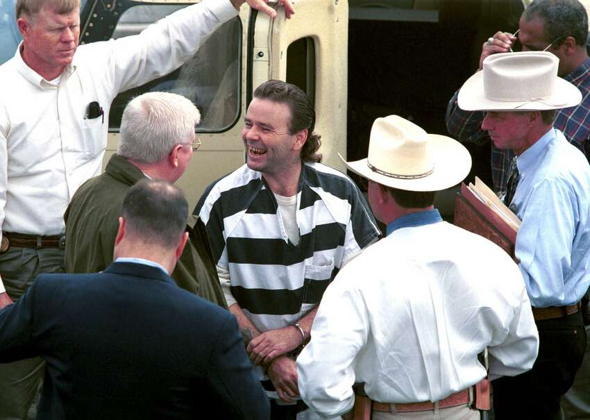 Tommy Lynn Sells (center) laughs with law enforcement officers after getting off a plane at Central Flying Service in Little Rock, Ark., on March 22, 2000. Sells was brought to Little Rock by Texas Rangers to talk to authorities about two murders he claims to have committed in Little Rock. The killings are among 13 that Tommy Lynn Sells says he carried out in seven states.