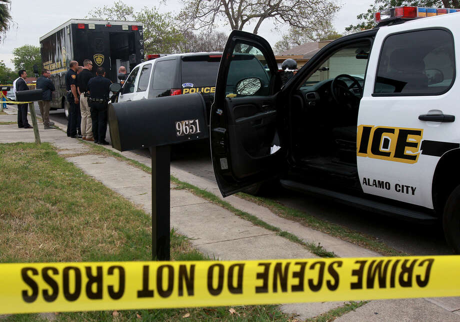 San Antonio police investigate the scene of a double murder-suicide in March 2013. The SAPD reported this week that 2013's murder numbers were down from 2012. Photo: San Antonio Express-News / File Photo / ©San Antonio Express-News