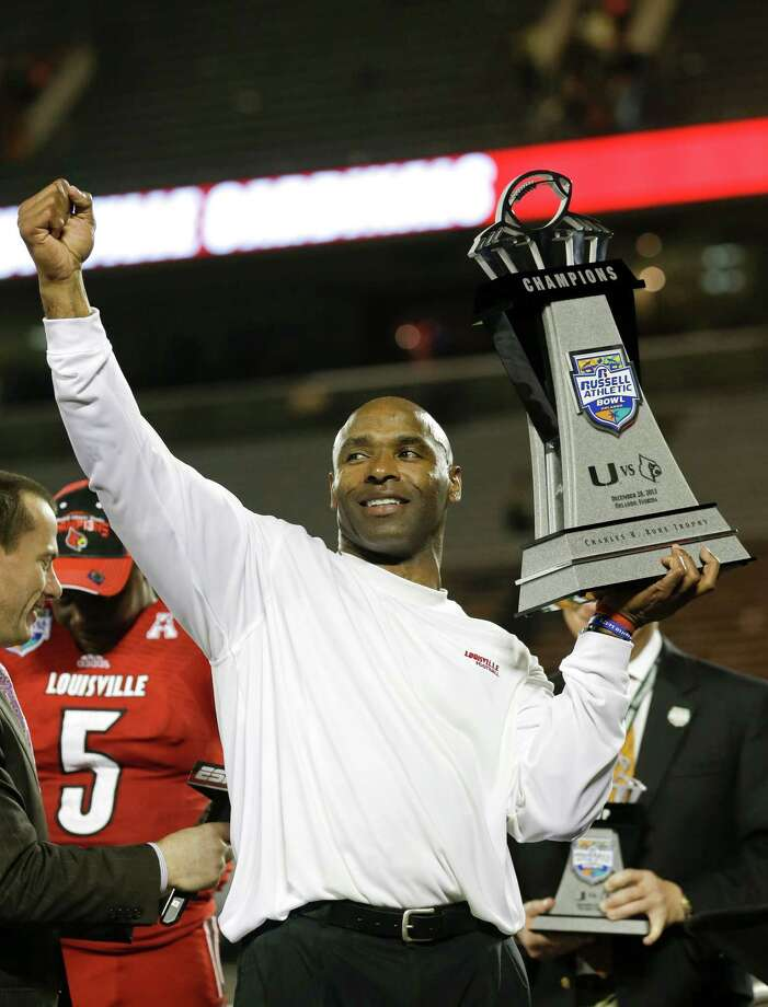 Louisville coach Charlie Strong holds the trophy after Louisville defeated Miami 36-9 in the Russell Athletic Bowl NCAA college football game in Orlando, Fla., Saturday, Dec. 28, 2013.(AP Photo/John Raoux) Photo: John Raoux, STF / AP
