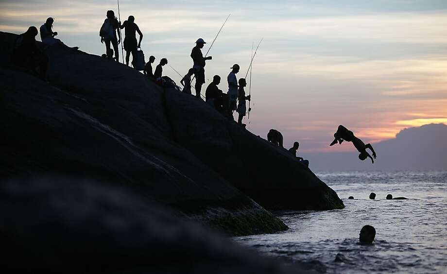 Hey, you're scaring the fish! A swimmer launches himself off the rocks at Arpoador in Rio de Janeiro, no doubt irking anglers hoping 
