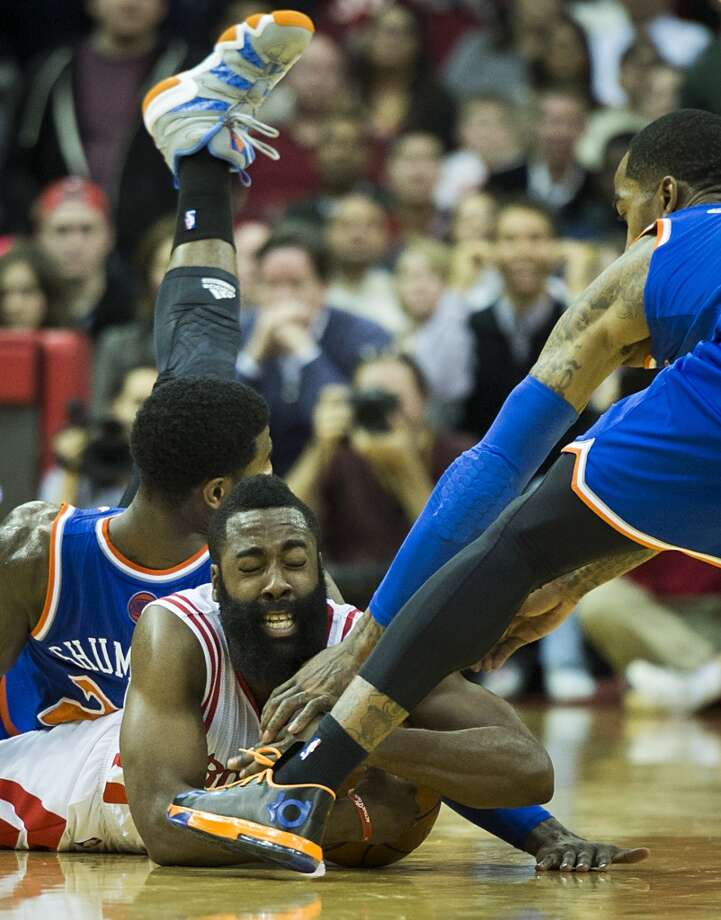 Rockets guard James Harden wrestles for a loose ball against Knicks shooting guards Iman Shumpert (21) and J.R. Smith. Photo: Smiley N. Pool, Houston Chronicle