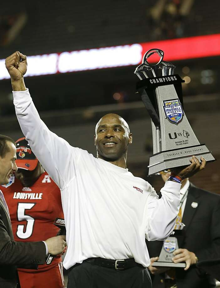 Louisville coach Charlie Strong holds the trophy after Louisville defeated Miami 36-9 in the Russell Athletic Bowl NCAA college football game in Orlando, Fla., Saturday, Dec. 28, 2013.(AP Photo/John Raoux) Photo: John Raoux, Associated Press