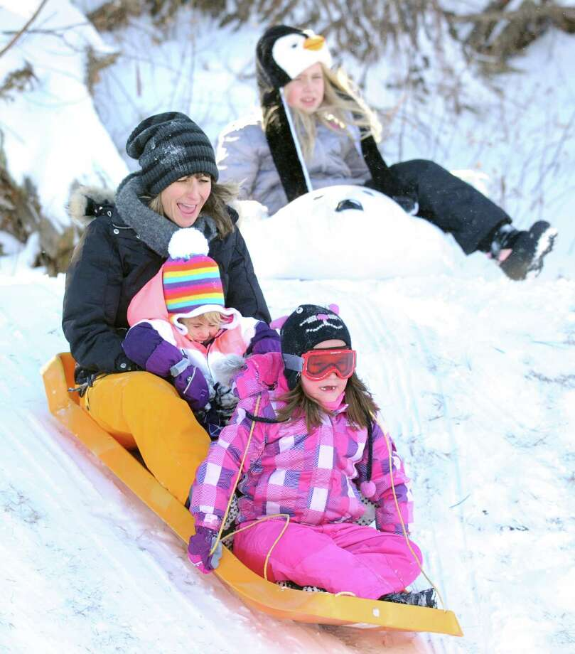 Flynn Tauber, 6, of Greenwich, holds down the front position on the sled as Elysia Borrelli takes the back while holding onto her daughter, Maryn, 4, while sled riding at the Western Greeenwich Civic Center, Greenwich, Conn., Friday afternnon, Jan. 3, 2014, during the aftermath of the snow storm that hit the area. Photo: Bob Luckey / Greenwich Time