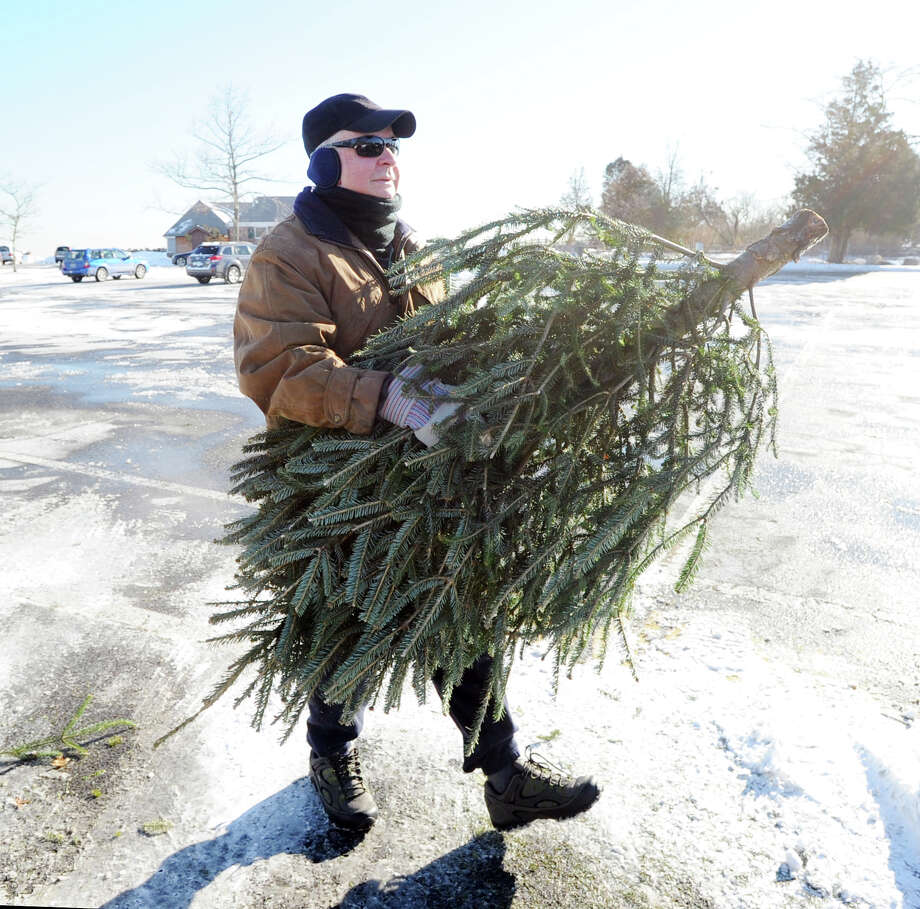 Al Amato of Old Greenwich unloads his Christmas tree from the trunk of his car before placing it in the recycling pile at Greenwich Point, Saturday morning, Jan. 4, 2014. According to the Town of Greenwich website, undecorated trees can be dropped off at four sites, Byram Park, Bruce Park (children's parking lot), Greenwich Point and the Holly Hill Resource Recovery Facility. Disposal times are 8 a.m. to 4 p.m., all week,  except for Holly Hill, which is 7 a.m. to 3 p.m. Monday - Friday and Saturday from 7 a.m. to noon. The deadline for returning trees is Jan. 31st except for Holly Hill. The wood chips can be used by residents as mulch or compost. Tree chips retained by the Town will be used in parks as mulch for trails in woodlands, shrub beds and soil stabilization. Photo: Bob Luckey / Greenwich Time