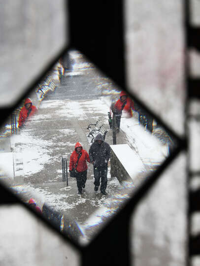 Snow falls on Main St. as seen through a library window in Stratford, Conn, on Monday, January 28, 2
