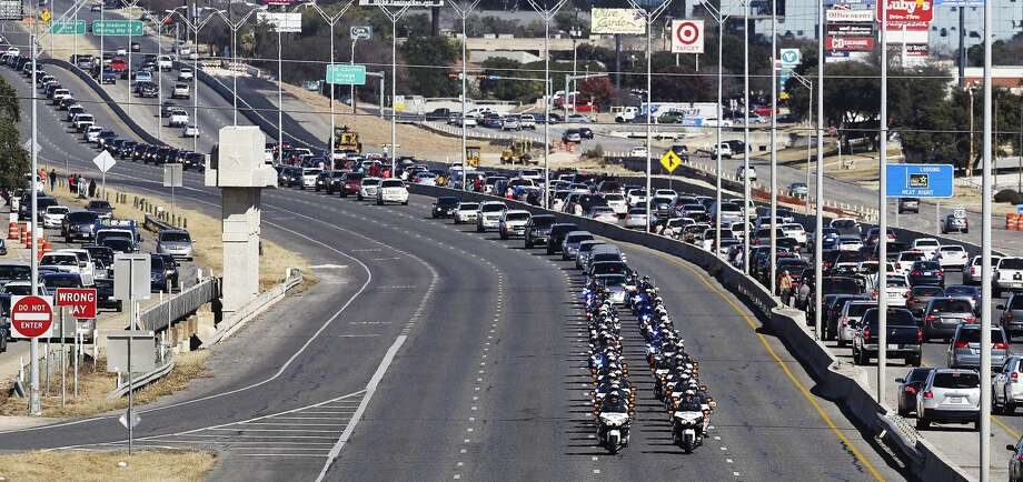 A procession for fallen San Antonio police officer Robert Deckard is led by SAPD motorcycles on Saturday, Jan. 4, 2014. Deckard was shot when in pursuit of two armed robbery suspects on Dec. 8 and died 13 days later. Family, friends and fellow police officers gathered at Cornerstone Church for a service and then a large procession went to Deckard's final resting place at Mission Park South. Photo: Kin Man Hui, Express-News