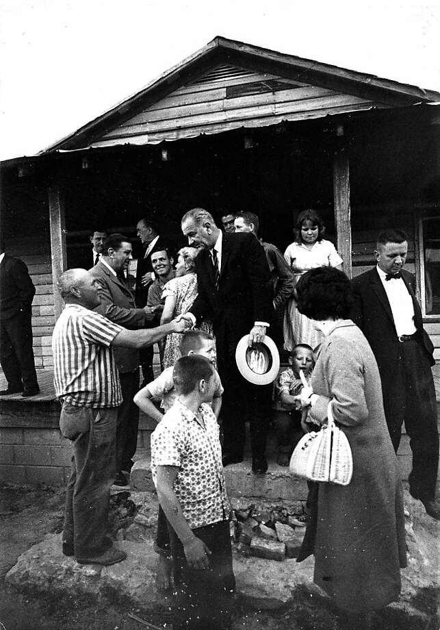 FILE -- President Lyndon B. Johnson, center, meets with residents of an impoverished community in 1964. Johnson's war on poverty is seen as a failure to many Americans, falling only four percent over two generations, flaring debate over the government's role in social programs as  inequality and poverty levels remain as acute as they were in the Roaring Twenties. (George Tames/The New York Times) Photo: George Tames, New York Times