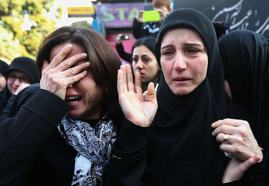 The mother of Ali Khadra, right, who was killed Thursday by a bomb explosion, mourns as she attends her son's funeral procession in the southern suburb of Beirut, Lebanon, Saturday, Jan. 4, 2014. An explosion tore through a crowded commercial street Thursday in a south Beirut neighborhood that is bastion of support for the Shiite group Hezbollah, killing several people, setting cars ablaze and sending a column of black smoke above the Beirut skyline. (AP Photo/Hussein Malla) Photo: Hussein Malla, Associated Press