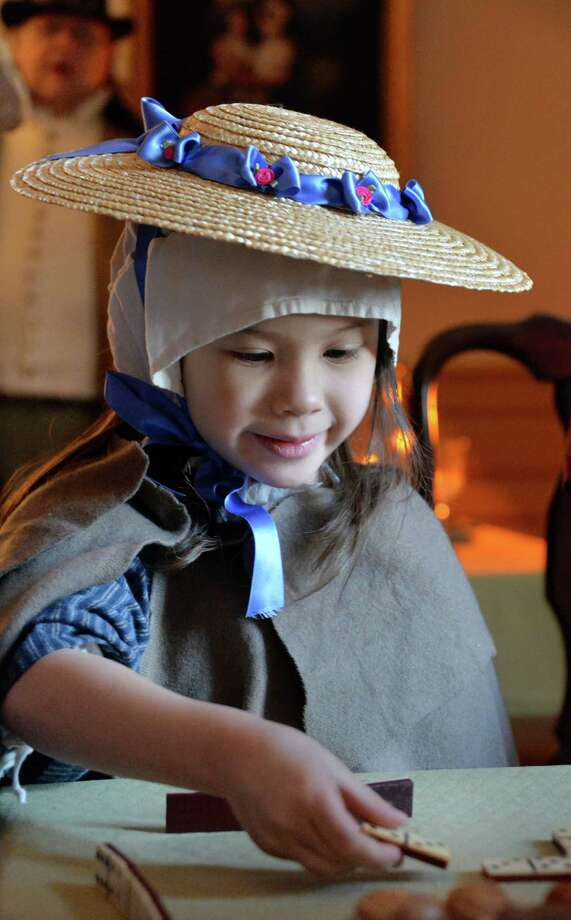 Four-year-old reenactor Lyra Lenigk of Niskayuna plays dominoes during the annual Twelfth Night Celebration at the Schuyler Mansion State Historic Site Saturday Jan. 4, 2014, in Albany, NY.  (John Carl D'Annibale / Times Union) Photo: John Carl D'Annibale / 00025218A