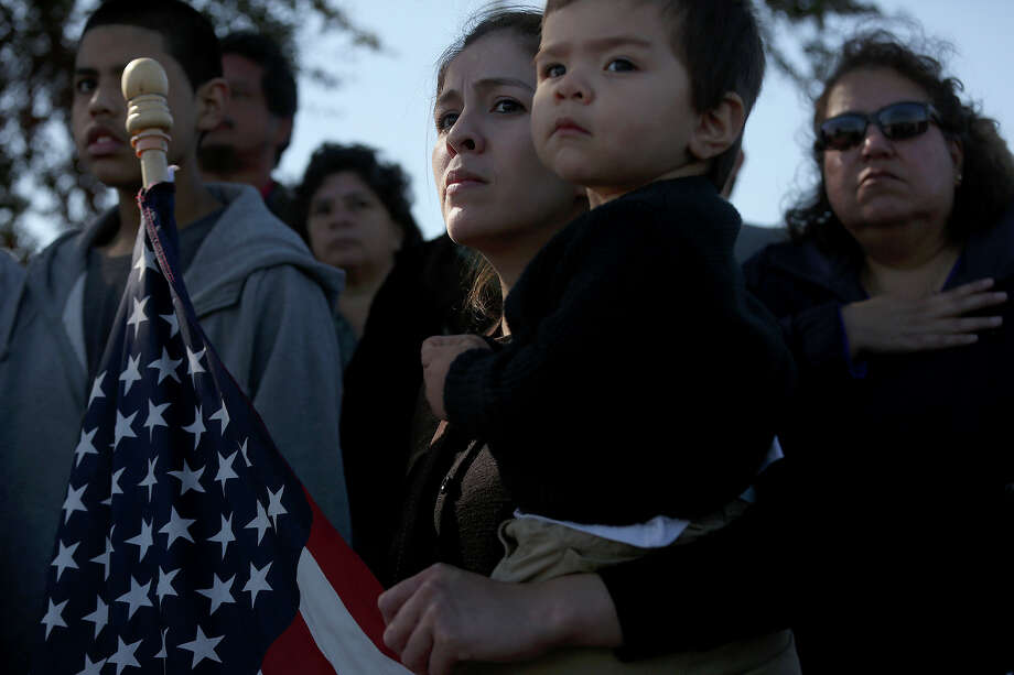 Maria Posada holds her son, Dylan Dominguez, 16 months, as they watch the funeral procession for Officer Robert Deckard arriving at Mission Burial Park South in San Antonio on Saturday, January 4, 2014. Posada's husband and Dylan's father, SAPD officer Juan Dominguez, was in the procession. Photo: Lisa Krantz, San Antonio Express-News / San Antonio Express-News