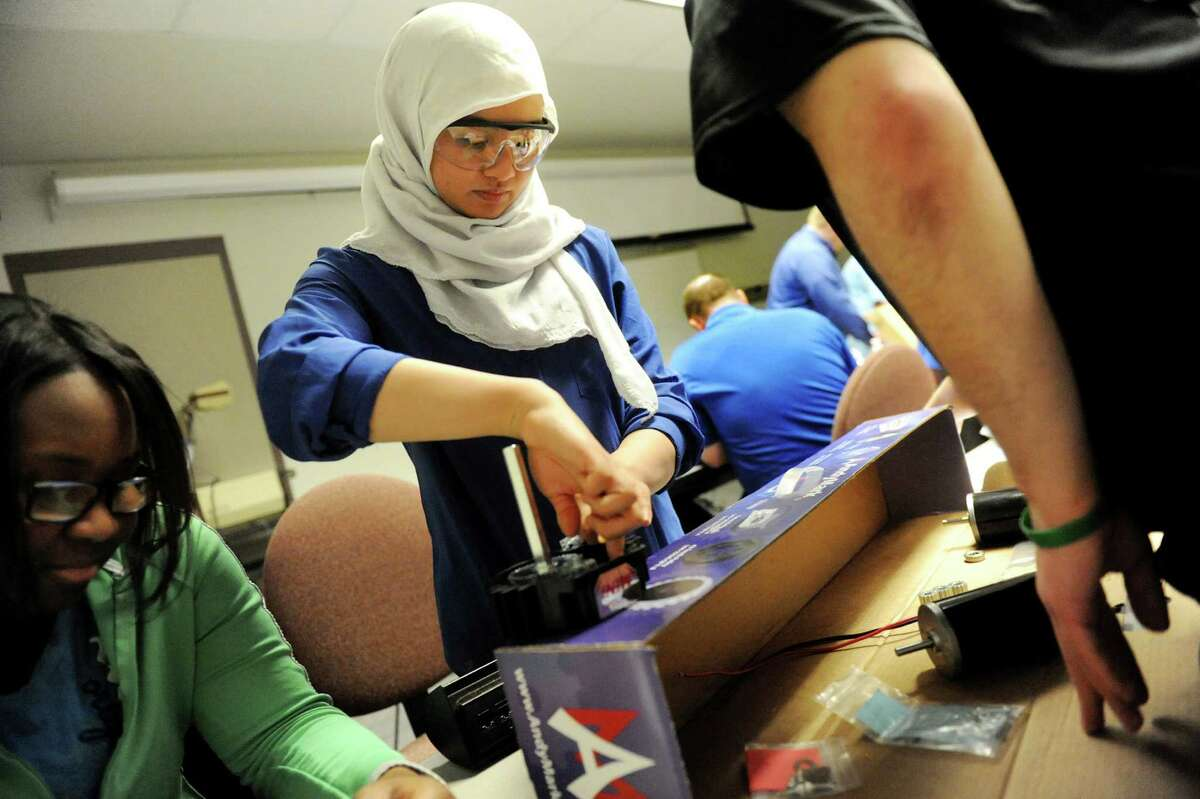 Nabihah Azhari, 16, center, works on a robot's gear box with the Troy High team during the 2014 FIRST Robotics Competition on Saturday, Jan. 4, 2014, at Rensselaer Polytechnic Institute in Troy, N.Y. Students with FIRST Robotics teams will design, build and test a robot. (Cindy Schultz / Times Union)