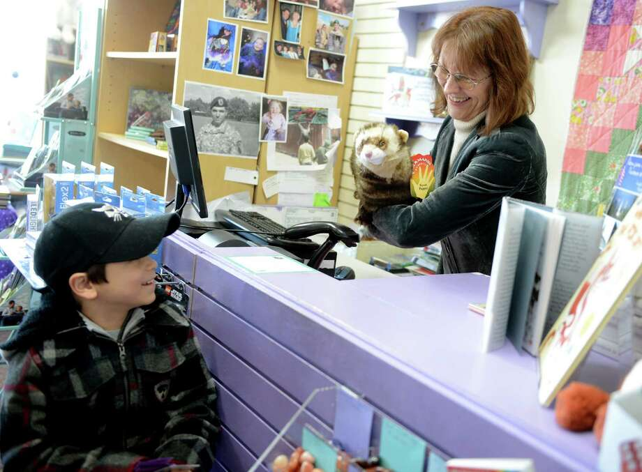 Linda Devlin shows customer Trey Migliarese, 8, of Monroe, how to animate his new stuffed puppet Saturday, Jan. 4, 2013 at her book store, Linda's Story Time in Monroe, Conn. Photo: Autumn Driscoll / Connecticut Post